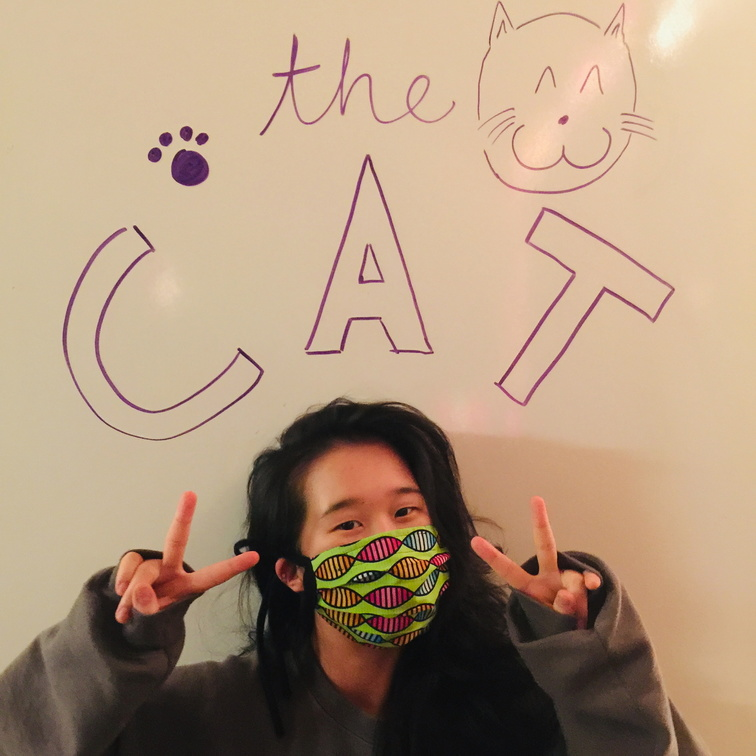 Masked volunteer standing if front of theCAT logo